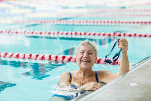 mujer mayor en la piscina tomando descanso de las vueltas de natación - vuelta completa fotografías e imágenes de stock