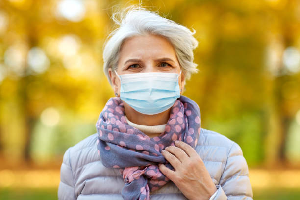 senior woman in protective medical mask at park stock photo
