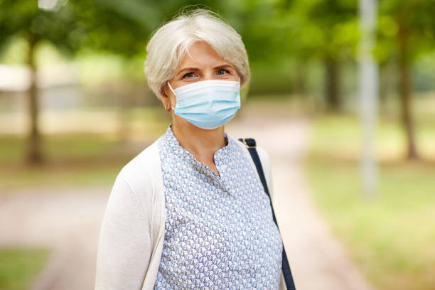 senior woman in protective medical mask in park stock photo