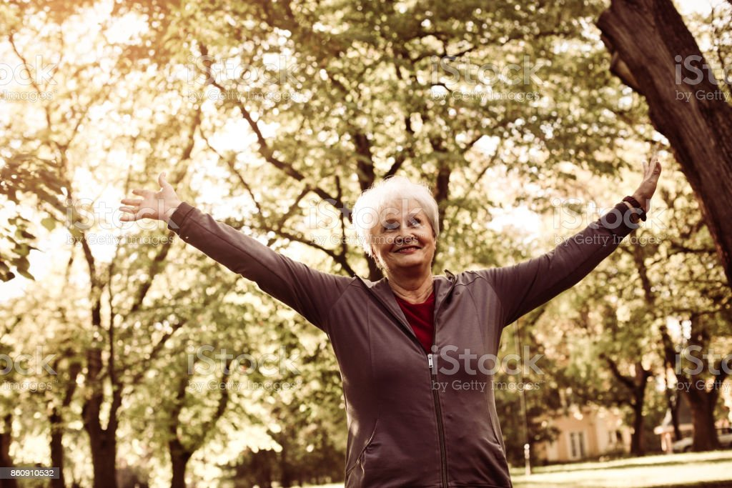 Senior woman in sports clothing enjoying in forest after exercising