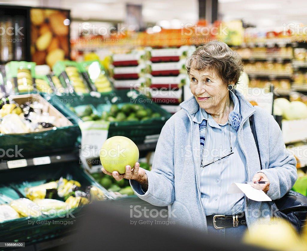 Senior woman in supermarket holding grapefruit smiles royalty-free stock photo