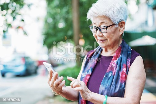 istock Senior woman in the city using phone to call taxi 974679746