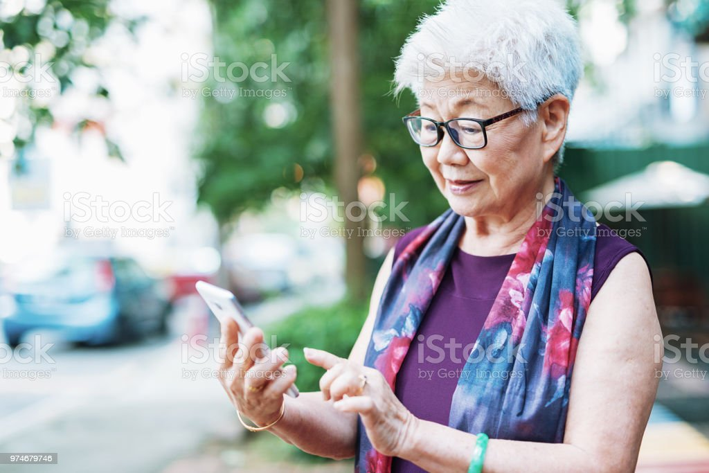 Senior woman in the city using phone to call taxi stock photo