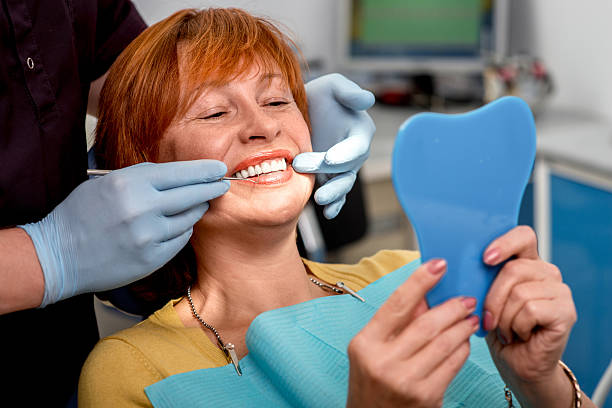 Senior woman in the dental office. Smiling senior woman with new dental implants sitting in the dental office and looking at the mirror implant stock pictures, royalty-free photos & images