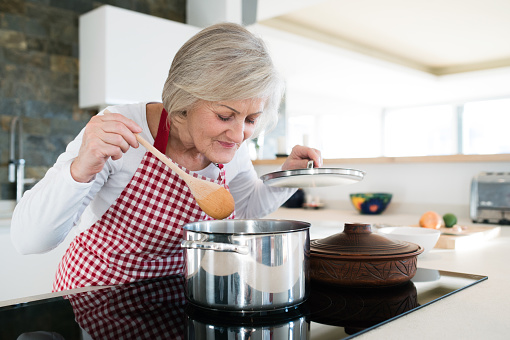 Senior woman in the kitchen cooking, mixing food in pot.