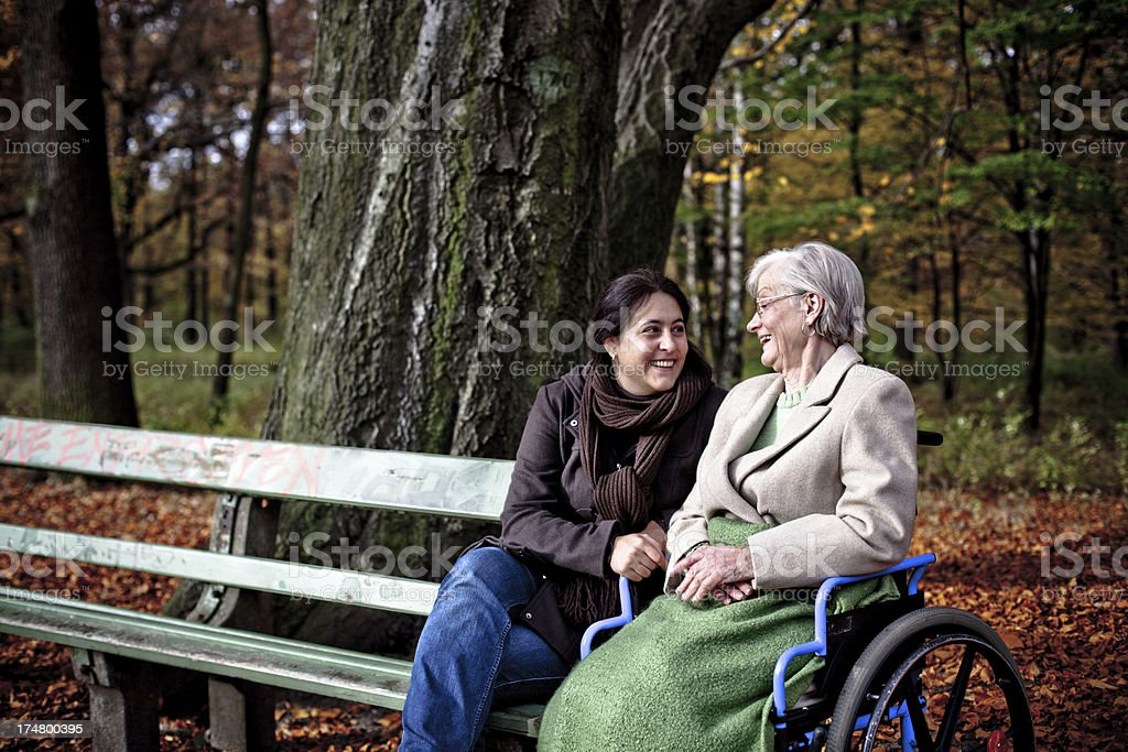 Senior woman in wheelchair and adult daughter in autumn park royalty-free stock photo