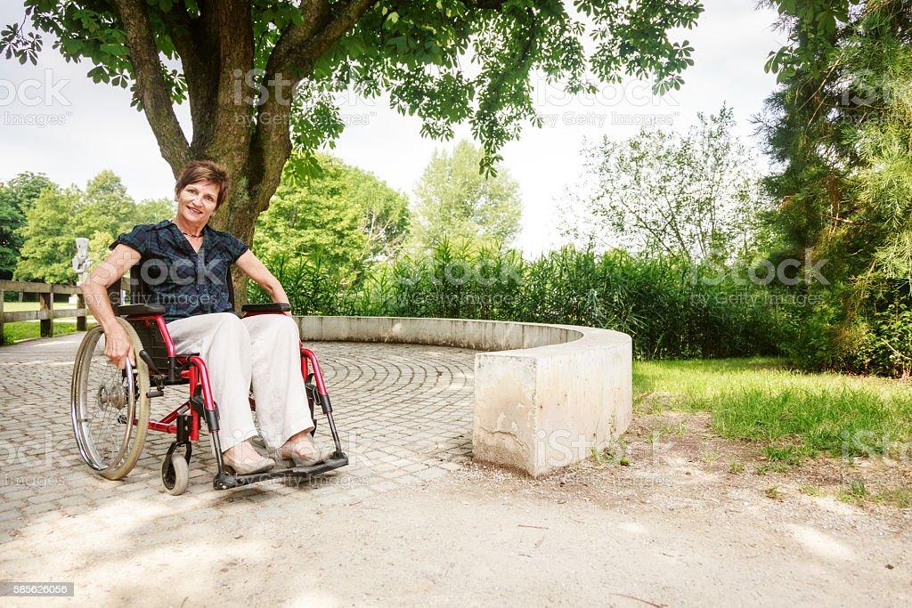 Senior woman in wheelchair, enjoying a day in the park - foto de stock
