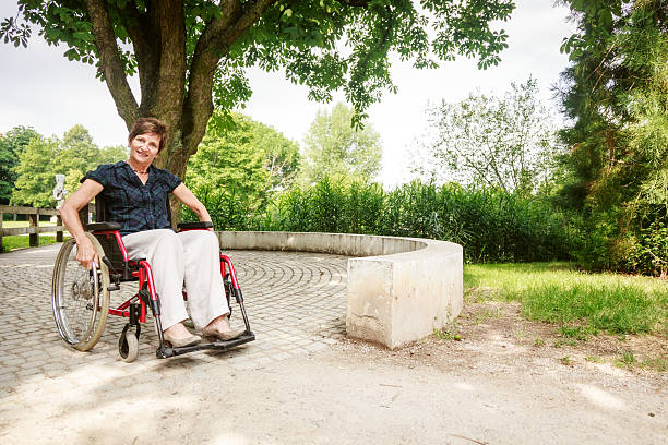 Senior woman in wheelchair, enjoying a day in the park - foto de stock