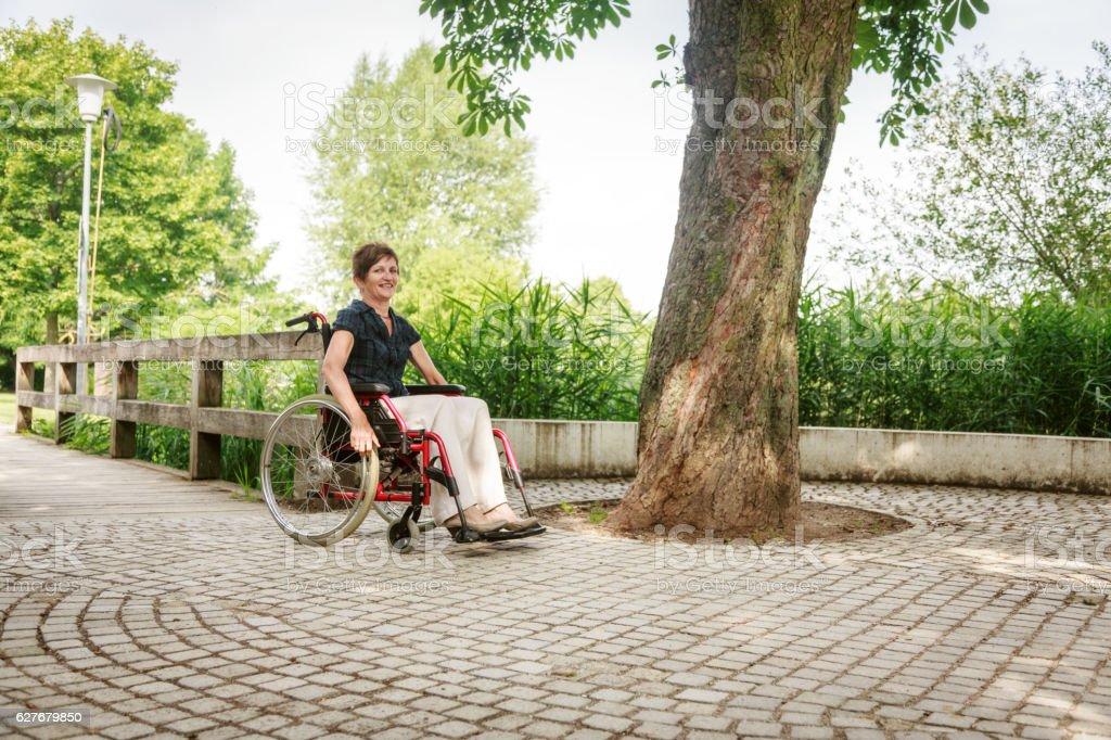 Mujer mayor en silla de ruedas, disfrutando de un día en el parque - foto de stock