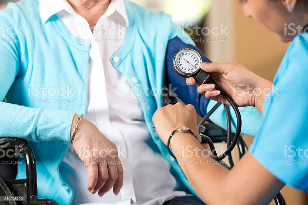 Senior woman in wheelchair getting her blood pressure taken stock photo