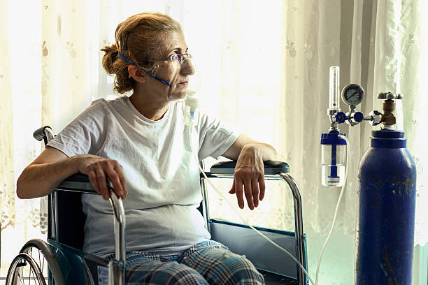 Senior Woman In Wheelchair Senior Woman In Wheelchair With Oxygen Mask. medical oxygen equipment stock pictures, royalty-free photos & images