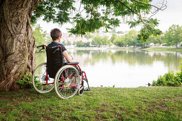 Senior woman in wheelchair Senior woman in wheelchair, enjoying time outdoors. paralysis stock pictures, royalty-free photos & images