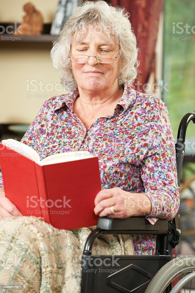 Senior Woman In Wheelchair Reading Book royalty-free stock photo