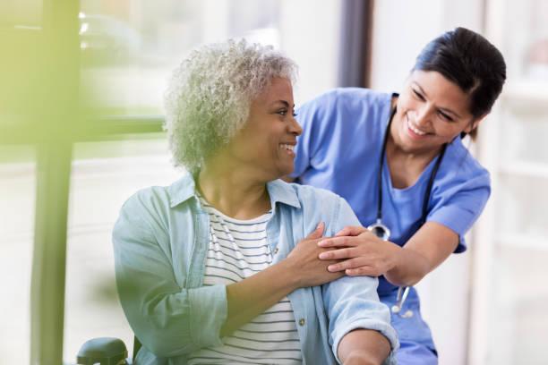 ältere frau im rollstuhl erhält medizinische hilfe für verletzungen - orthopädisches hilfsmittel stock-fotos und bilder