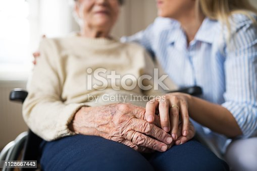 istock A senior woman in wheelchair with a health visitor at home at Christmas time. 1128667443