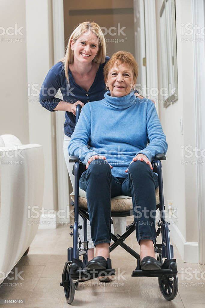 A senior woman sitting in a wheelchair at home with a caregiver...