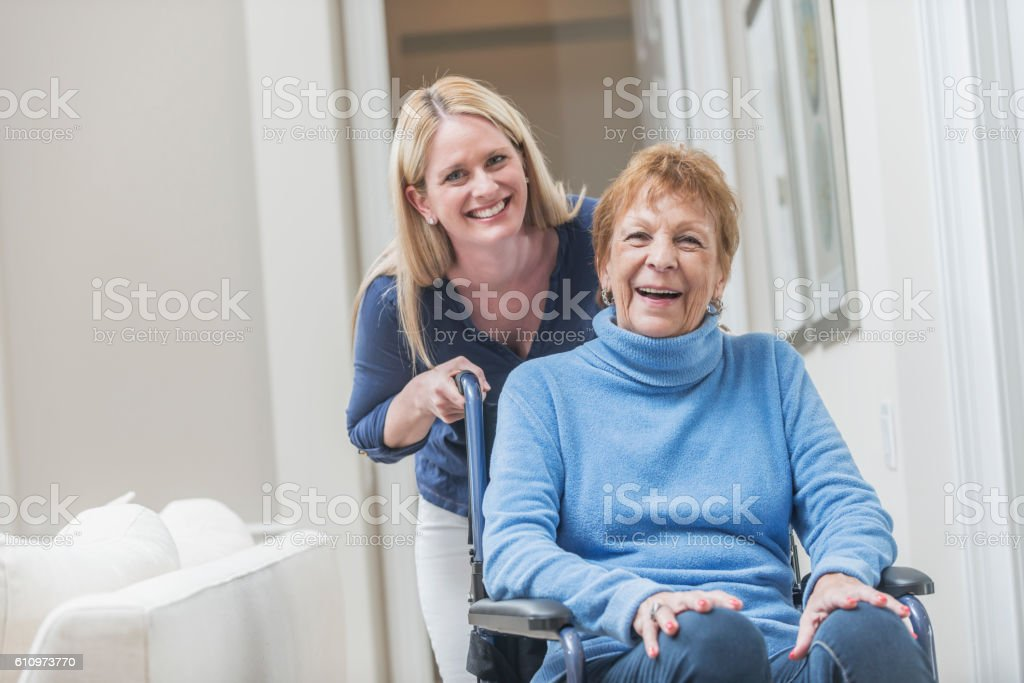 Senior woman in wheelchair with caregiver at home stock photo