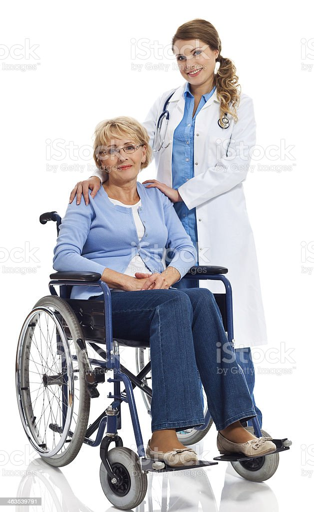 Senior woman in wheelchair with doctor Portrait of senior woman sitting in wheelchair with a young doctor standing next to her. Studio shot on white background. 60-69 Years Stock Photo