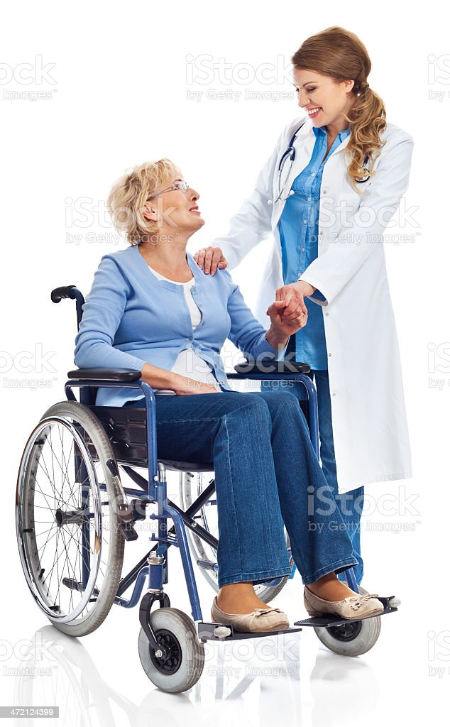 Senior woman in wheelchair with doctor Portrait of senior woman sitting in wheelchair talking with young female doctor. Studio shot on white background. 60-69 Years Stock Photo