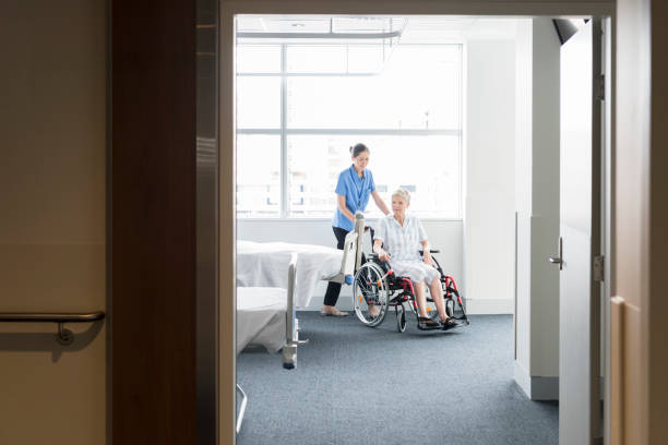 senior woman in wheelchair with female nurse on the ward - australian nurses stock photos and pictures