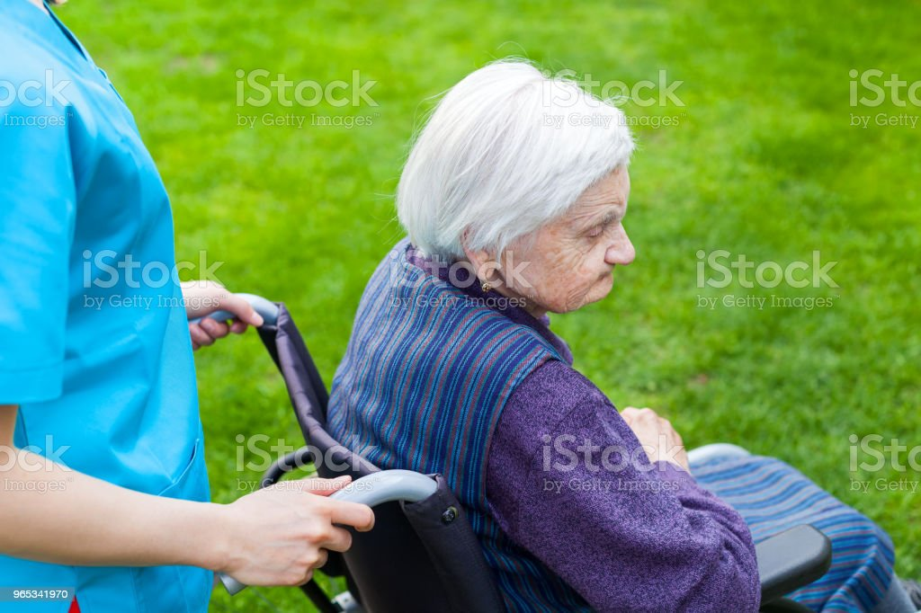 Senior woman in wheelchair with nurse zbiór zdjęć royalty-free