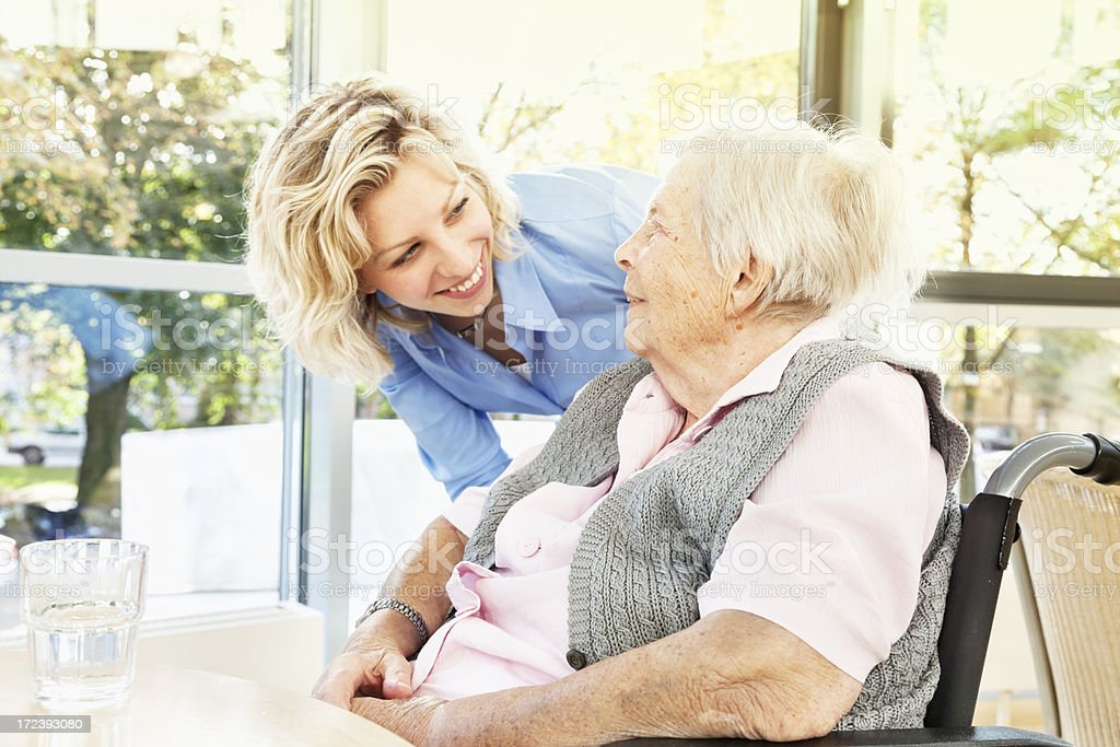 senior woman in wheelchair with young kind caregiver royalty-free stock photo