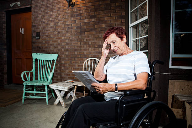 Senior woman in wheelchair worried about paying bills stock photo