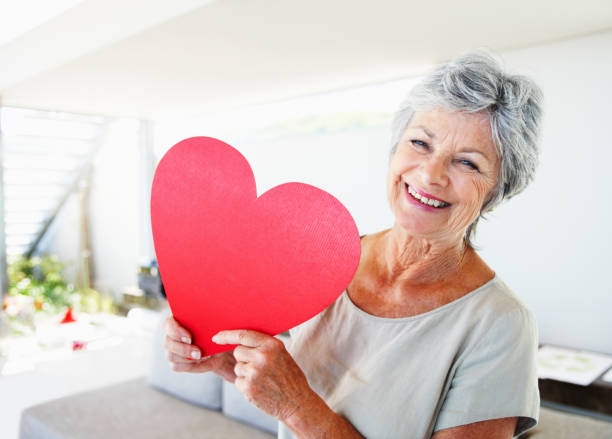 senior woman in white shirt holding a large paper heart - senior valentine stock photos and pictures