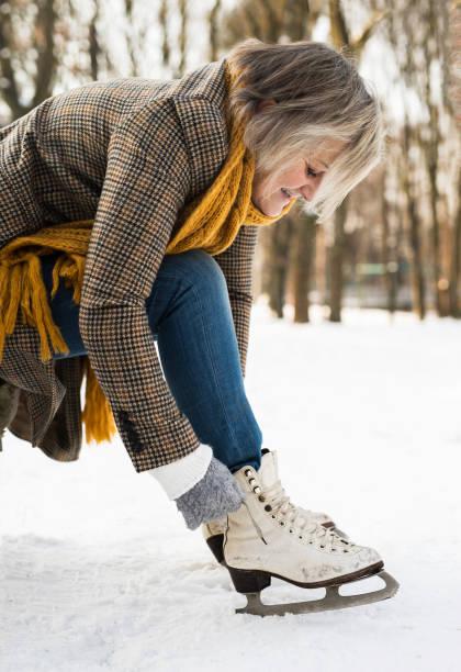 senior woman in winter clothes putting on old ice skates. - wintermantel damen wolle stock-fotos und bilder