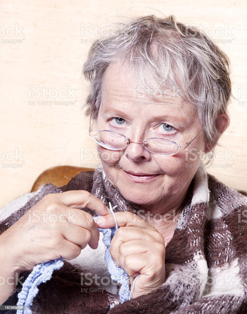 Senior woman in wollen scarf knitting. royalty-free stock photo