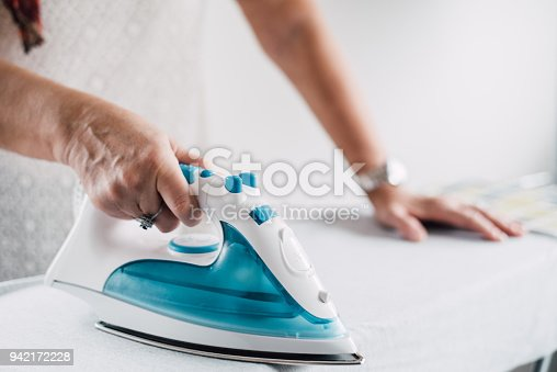 524159504 istock photo Senior woman ironing a shirt 942172228