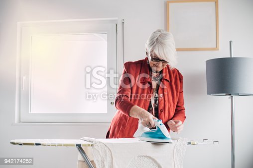 524159504 istock photo Senior woman ironing a shirt 942174252