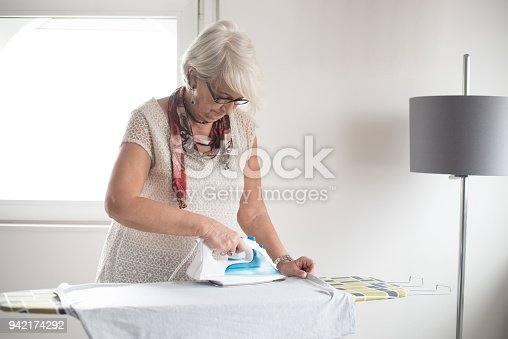524159504 istock photo Senior woman ironing a white shirt 942174292
