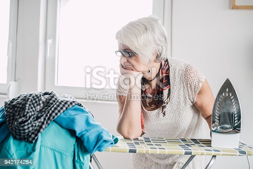 524159504 istock photo Senior woman ironing pile of laundry 942174284