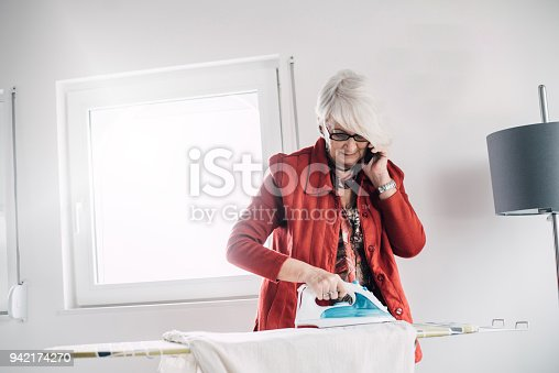 524159504 istock photo Senior woman ironing taking a call 942174270