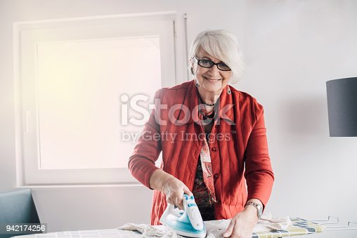 524159504 istock photo Senior woman ironing the laundry 942174256