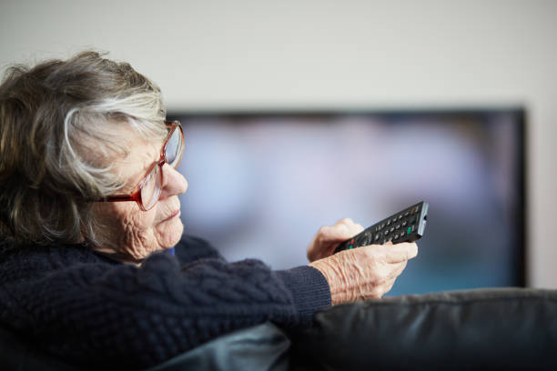 Senior woman irritated by her TV remote control stock photo