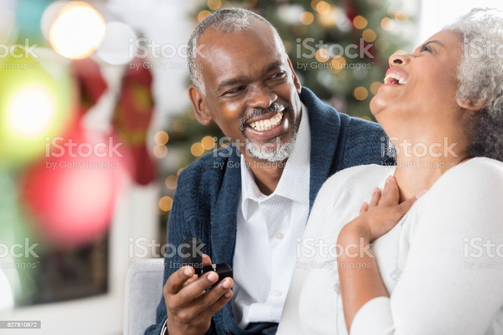 Senior woman is excited to receive jewelry at Christmastime stock photo