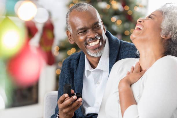 ältere frau ist begeistert, schmuck in der weihnachtszeit zu erhalten - verlobung was schenken stock-fotos und bilder