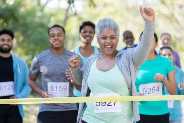 ältere frau wird zunächst auf die ziellinie in charity-rennen - laufveranstaltungen stock-fotos und bilder