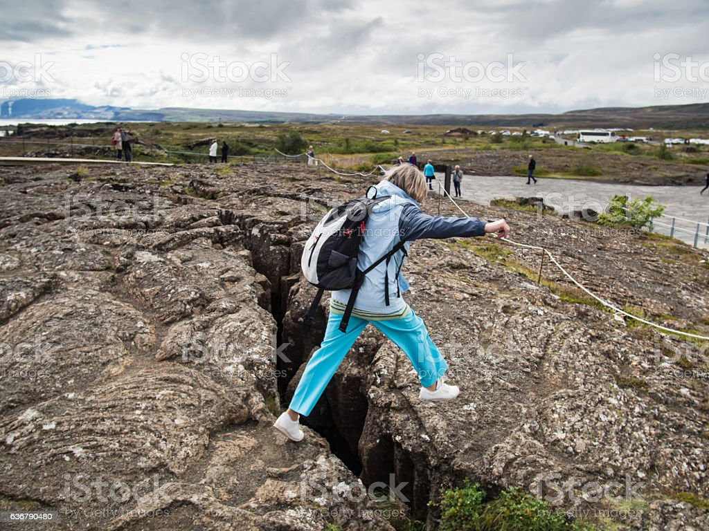 Senior woman is jumping over an earth gap stock photo