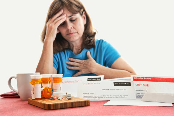 Senior Woman is Overwhelmed by Notices from Banks and Expensive Drugs stock photo