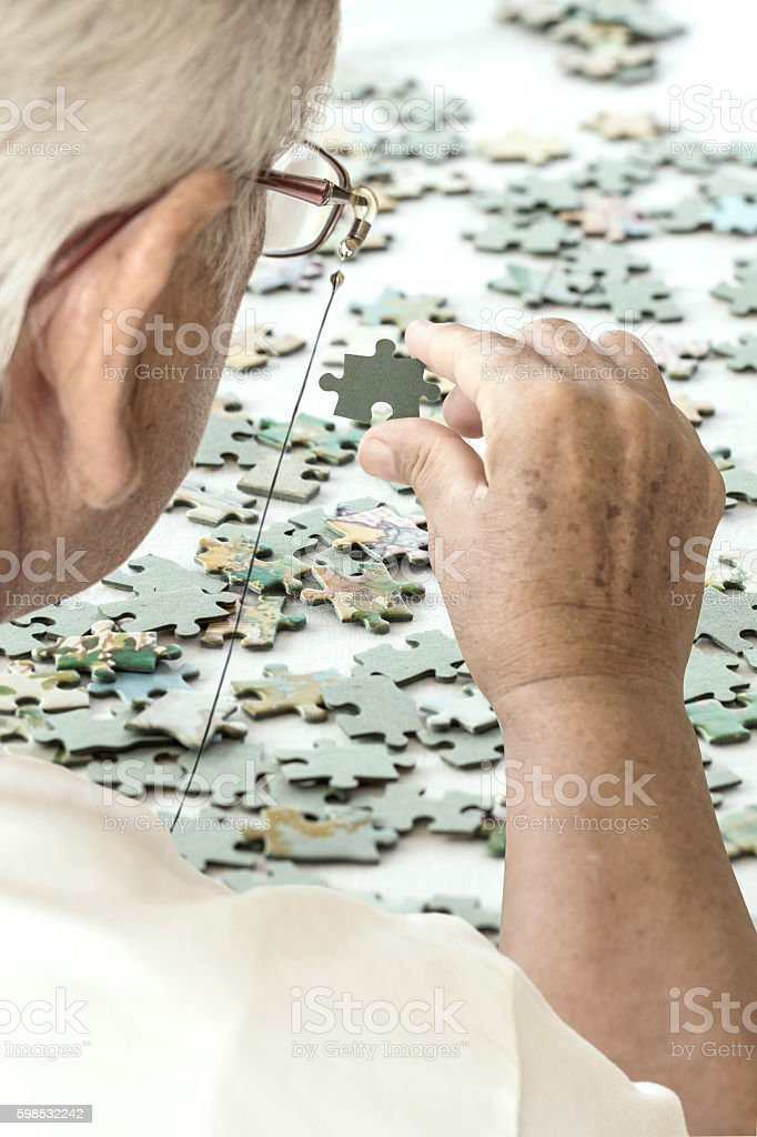 Senior Woman is Playing Puzzle. photo libre de droits