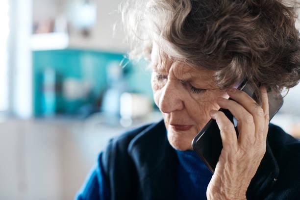 Senior woman is upset by phone conversation stock photo