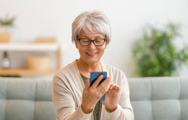 senior woman is using smartphone stock photo