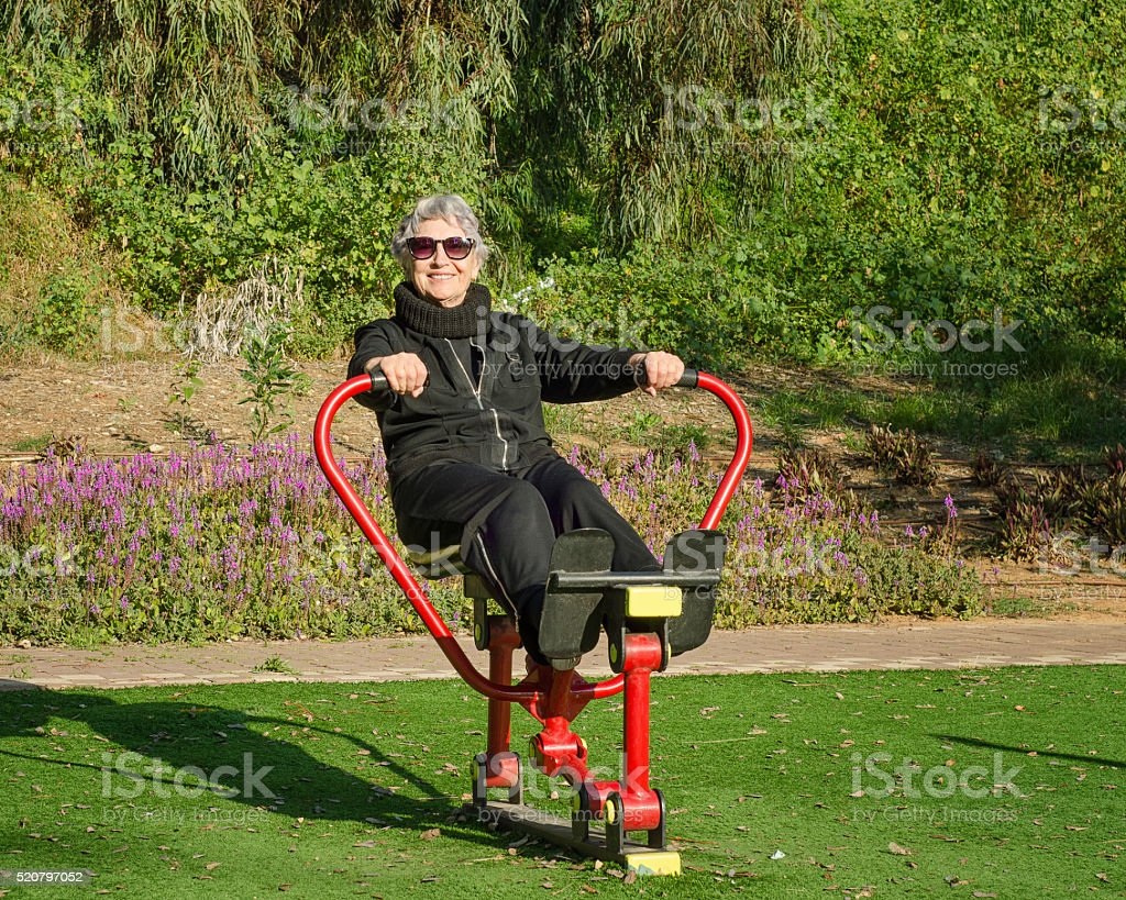 Senior woman is working out on a rowing trainer stock photo