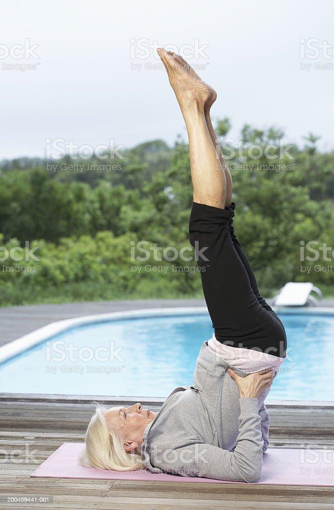 Senior woman is yoga position royalty-free stock photo