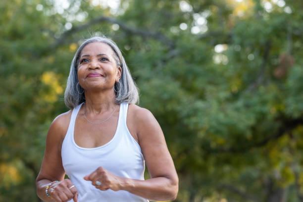 seniorin joggt im öffentlichen park - entspannungsübung stock-fotos und bilder