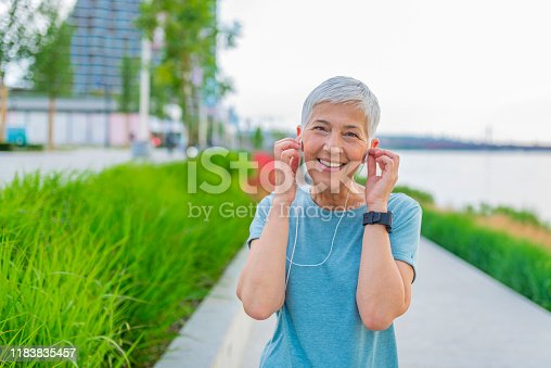 1057638814 istock photo Senior woman jogging on street during late afternoon 1183835457
