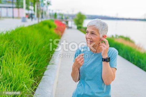 1057638814 istock photo Senior woman jogging outside with earphones on 1183835595